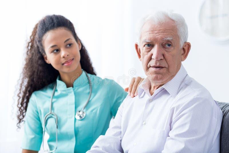 支持老人的女性医生 免版税库存图片