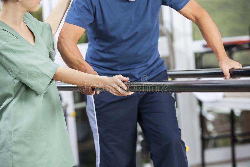 支持老人的生理治疗师走在平行之间 免版税图库摄影