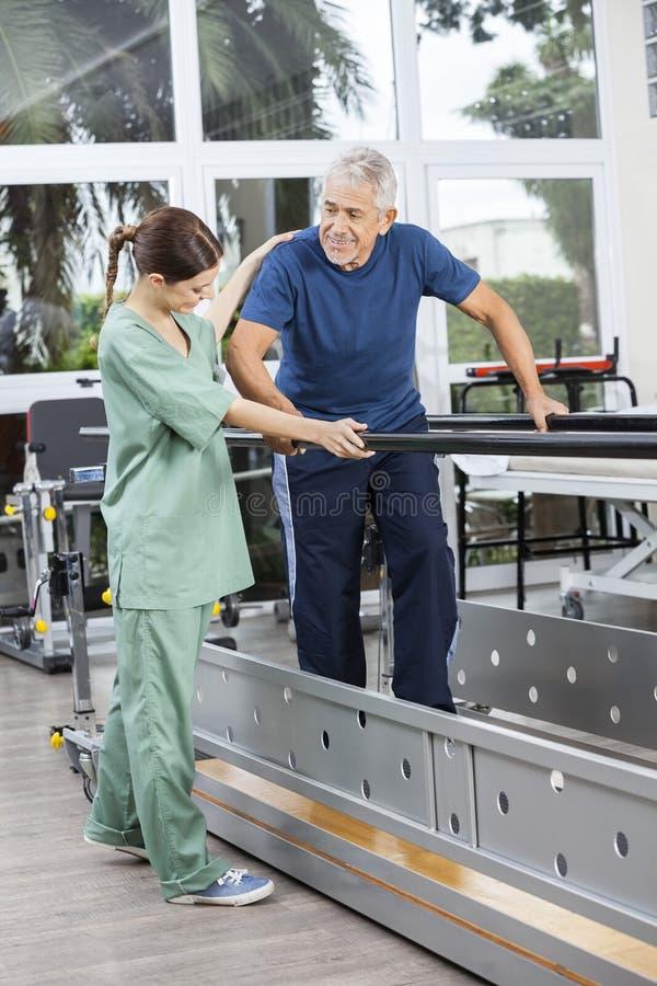 支持资深患者的生理治疗师走在Paral之间 免版税库存图片
