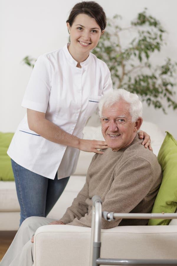 支持资深患者的年轻生理治疗师 库存图片