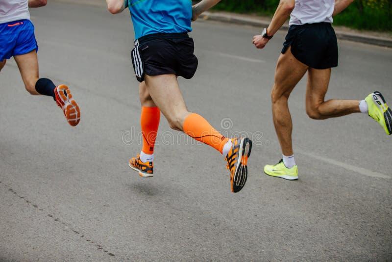 支持运行在城市街道上的三个人赛跑者 免版税库存照片