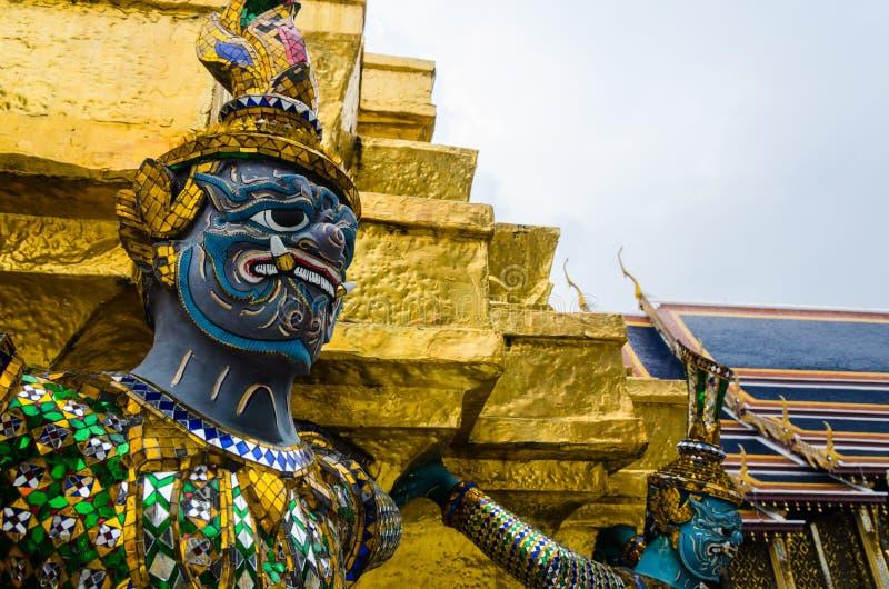 支持金黄塔的邪魔雕象在曼谷玉佛寺(鲜绿色菩萨的寺庙) 库存照片