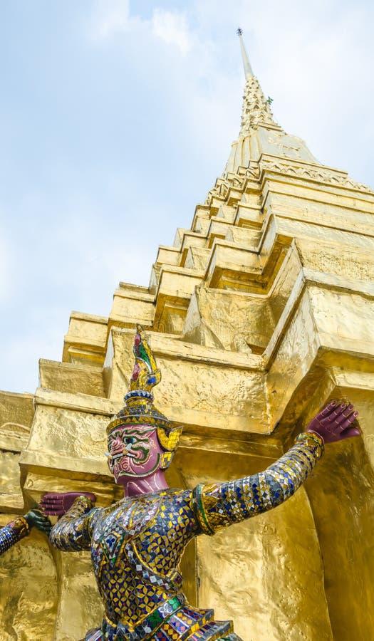 支持金黄塔的邪魔雕象 免版税图库摄影