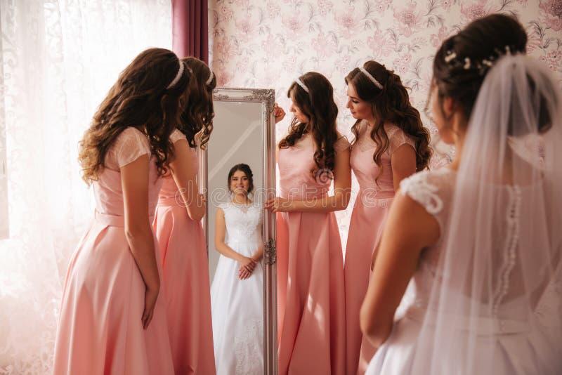 支持镜子的女傧相和帮助新娘看你自己 大镜子在家 同样礼服的愉快的女孩的 库存照片