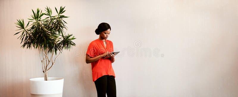 支持绿色持续力的黑色女性使用片剂 免版税库存图片