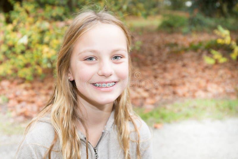 支撑牙少年女孩室外微笑的秀丽逗人喜爱青少年 免版税图库摄影