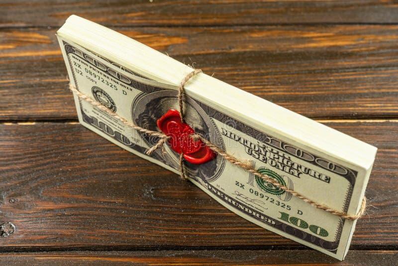 支柱金钱美元 充分的印刷品老牌 100美金 与封印和绳索的被密封的砖 库存照片