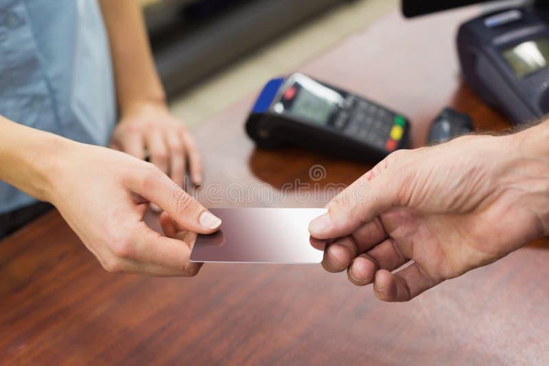 支付与信用卡的收款机的妇女 库存图片
