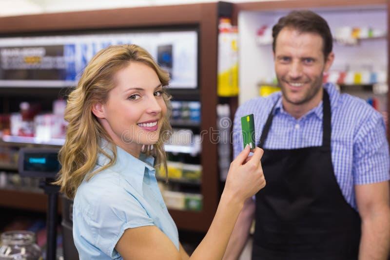 支付与信用卡的收款机的妇女 免版税库存照片