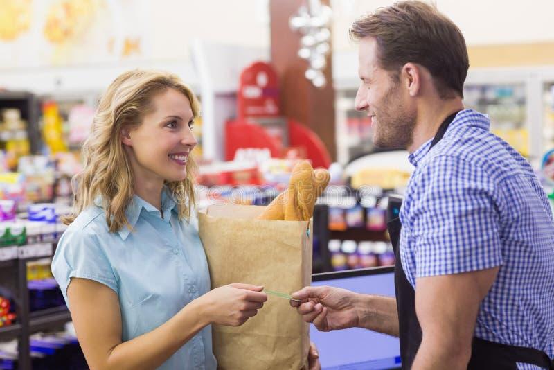 支付与信用卡的收款机的Smilingm妇女 库存图片