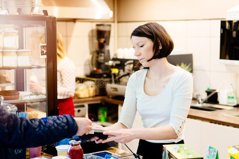 支付与信用卡的顾客在小商店 免版税库存照片