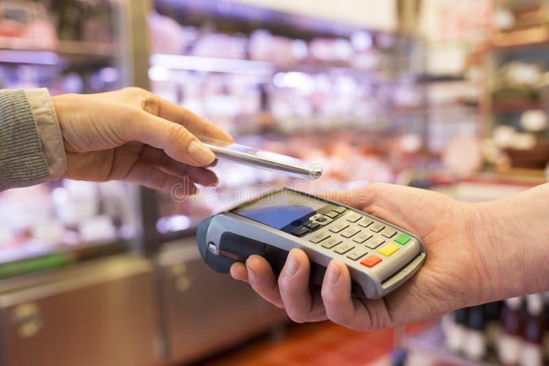 支付与在手机的NFC技术的妇女,在超级市场 免版税图库摄影