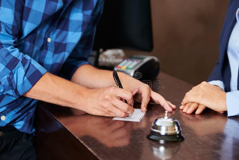 支付与检查的旅馆招待会的客人 图库摄影