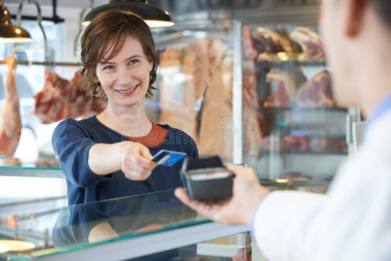 支付在肉店的女性顾客使用信用卡 库存图片