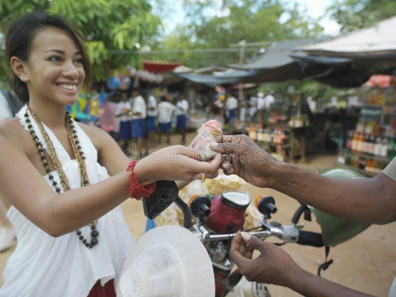 支付在街市上的微笑的妇女 库存照片