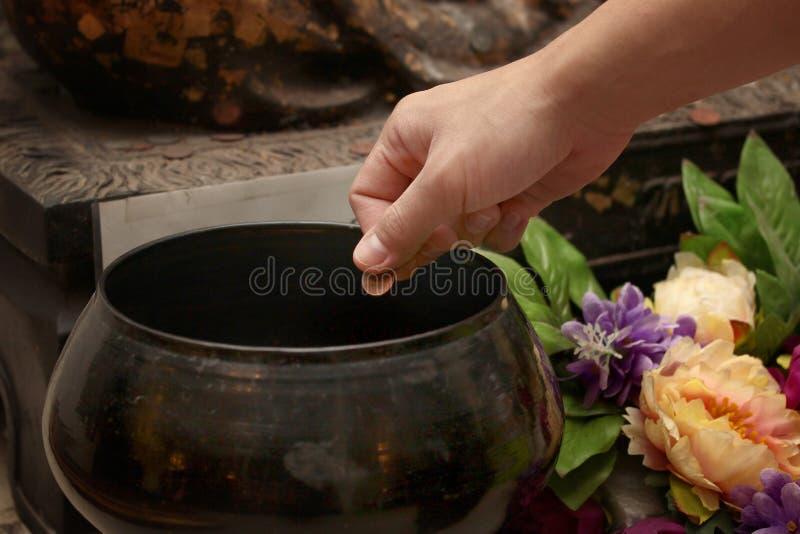 支付在109个修士碗的硬币用佛教崇拜方式 免版税库存图片