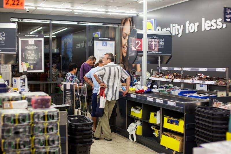 支付购物的顾客在超级市场 在现金的线 免版税库存图片
