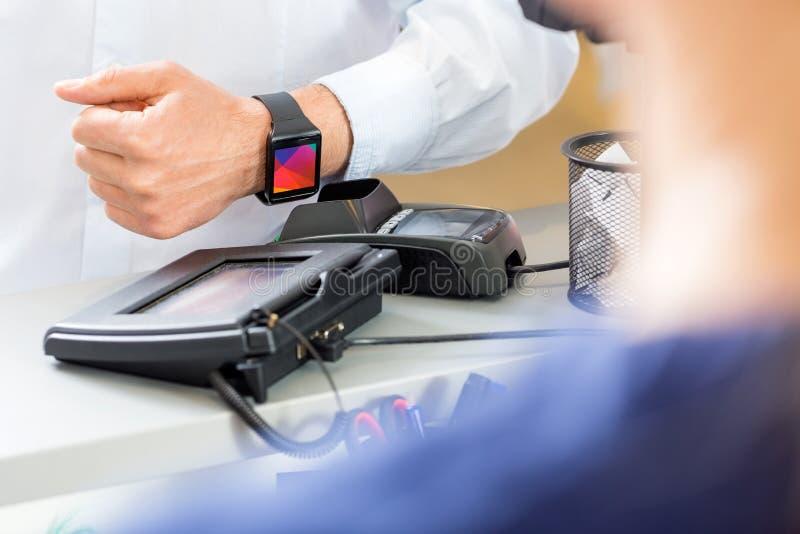 支付通过Smartwatch的顾客的中央部位在P的柜台 免版税库存照片