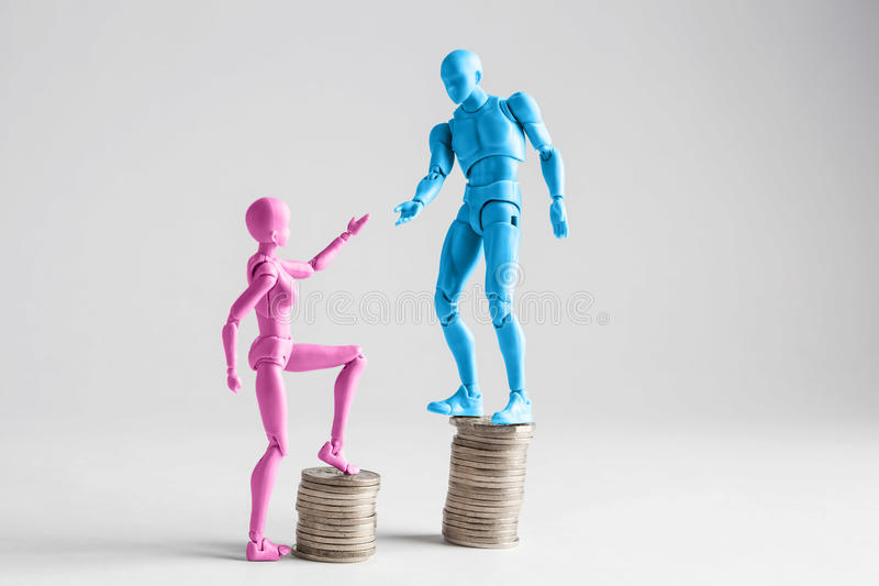 收入不平等概念显示与现实男性和女性小雕象和堆硬币 库存照片