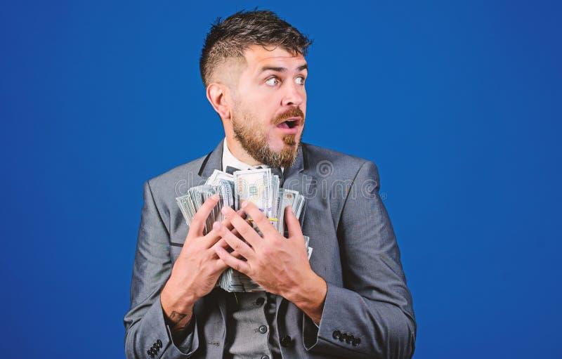 收入惊奇概念 人有胡子的商人举行堆金钱蓝色背景 惊奇的商人感觉象 免版税库存图片