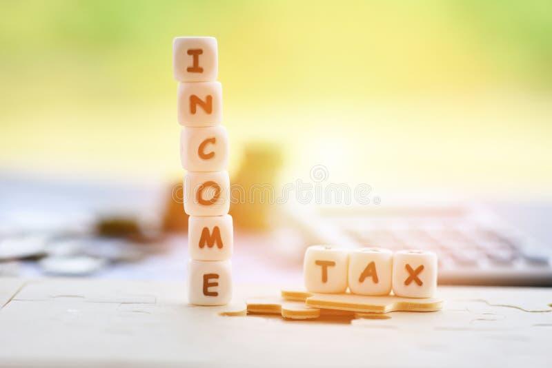 收入税单扣除在竖锯和计算器硬币的退款Concep/税词在发货票票据纸 免版税库存图片