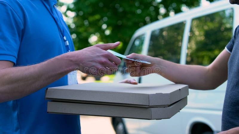 收到比萨发货的,食物交付,兼职的送货员金钱 免版税库存照片