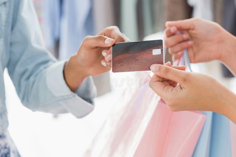 收到购物袋和信用卡的顾客的中间部分从女推销员 免版税库存图片