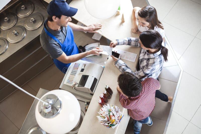 给收据的侍者站立与家庭的女性顾客 免版税库存图片