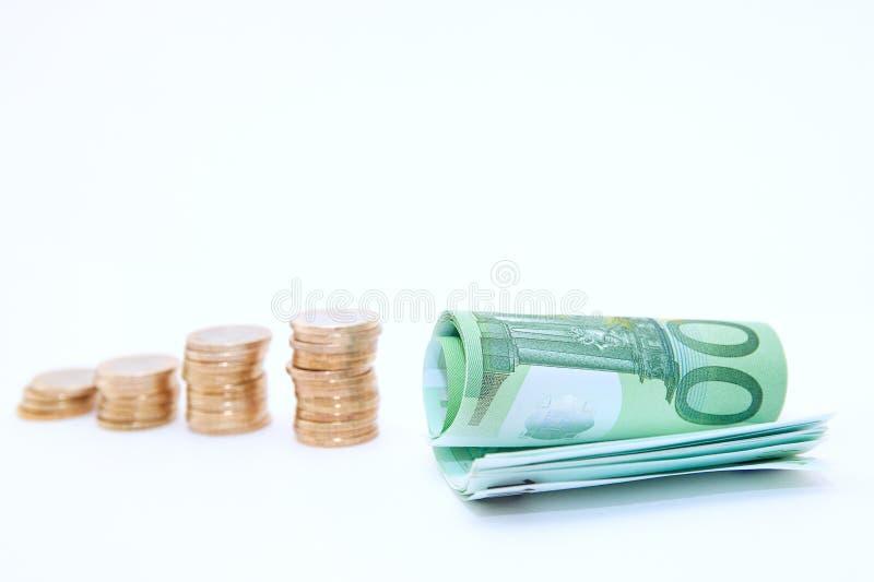 收支成长形式金黄堆对欧洲钞票的硬币在白色背景 免版税库存图片