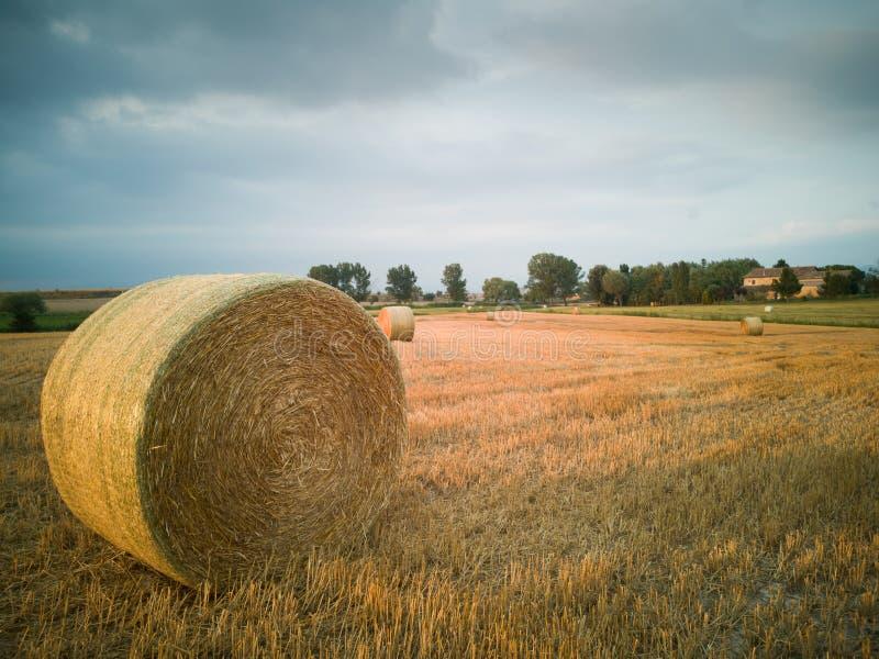 收获秸杆大包农舍风雨如磐的云彩视图 免版税图库摄影