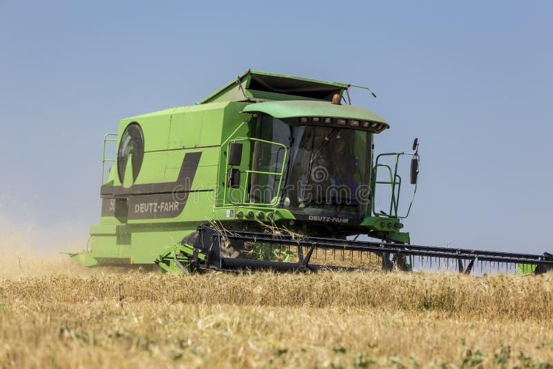 收获麦子的联合收割机在晴朗的夏日在希腊 免版税库存照片