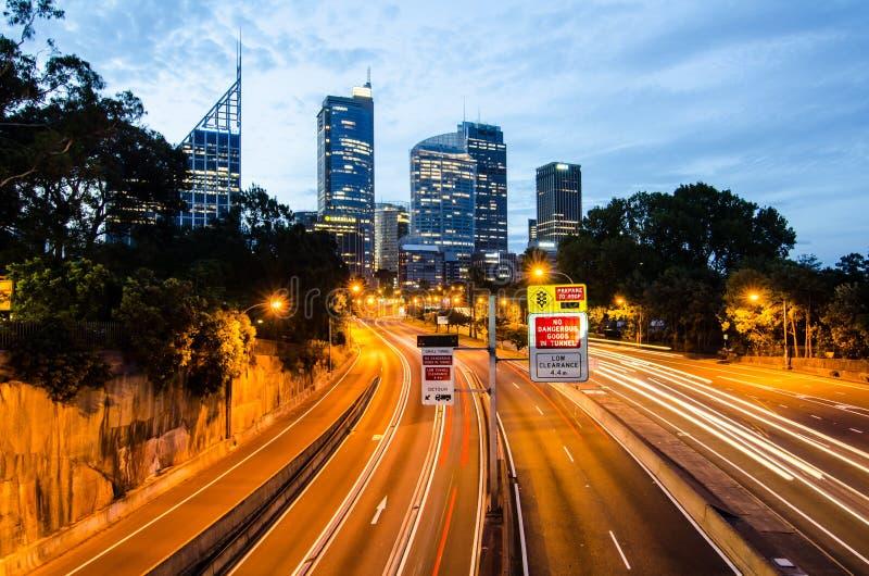 收费公路夜摄影有都市风景的在背景 免版税库存图片