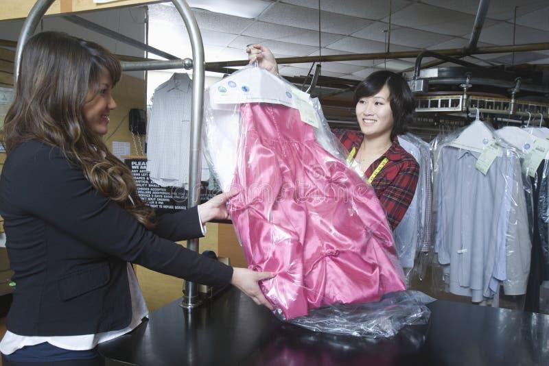 收集干净的礼服的顾客从在洗衣店的所有者 免版税库存图片