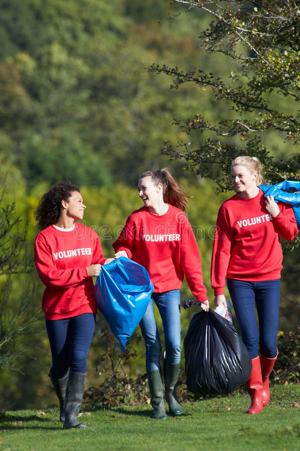 收集废弃物的小组女性志愿者 免版税库存照片