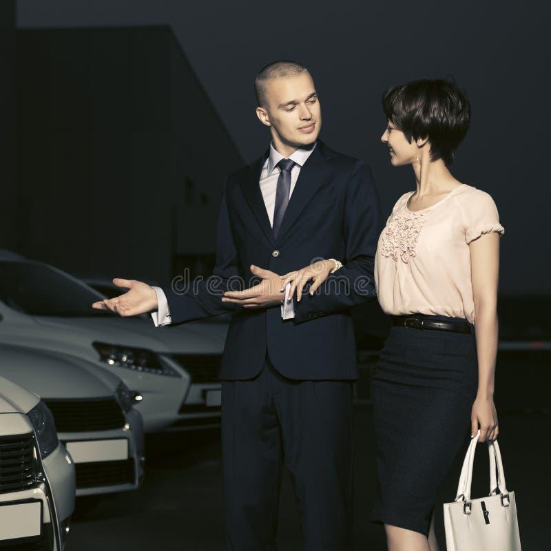 收集新的汽车的年轻时装业夫妇在经销权全部 库存照片