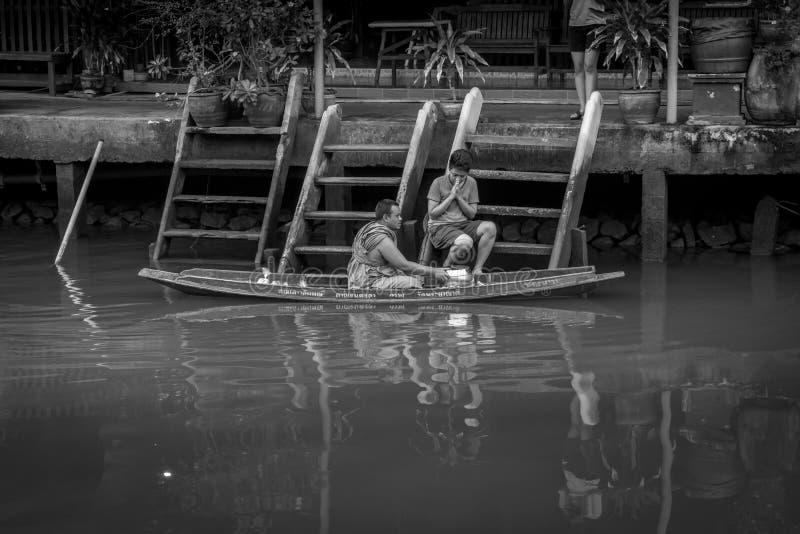 收集施舍的修士在Amphawa河 库存照片