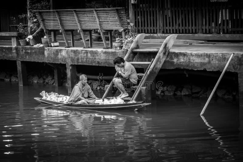 收集施舍的修士在Amphawa河 库存图片