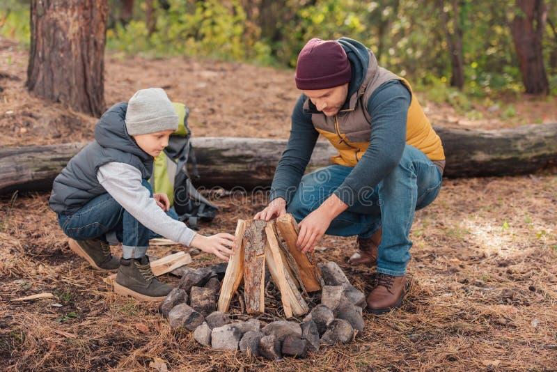 收集木柴和点燃篝火的父亲和儿子 免版税库存照片