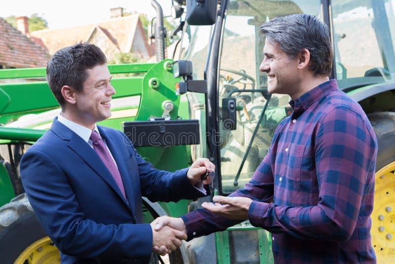 收集钥匙的农夫对新的拖拉机从商人 免版税库存图片