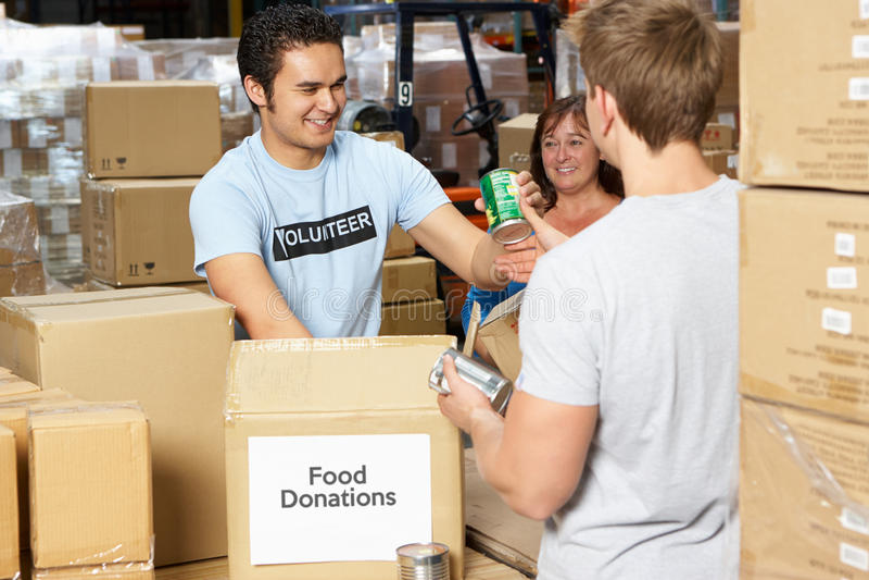 收集食物捐赠的志愿者在大商店里 免版税库存图片