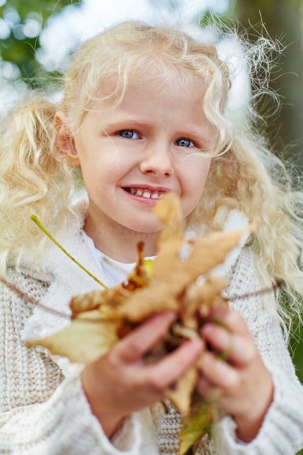 收集autmn叶子的白肤金发的小女孩 免版税库存图片