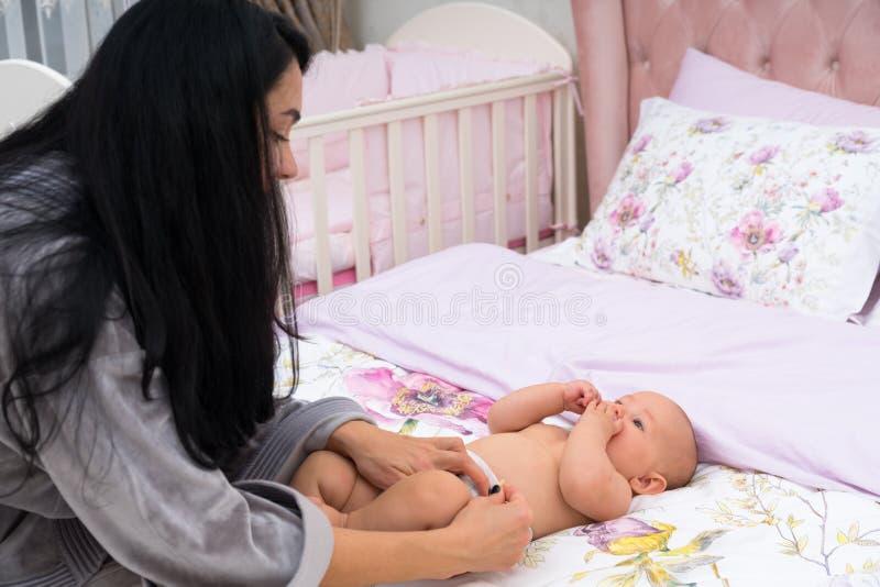 改变她的小小女儿的尿布母亲 免版税库存照片
