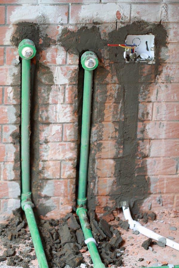 改造工程,在墙壁埋没pvc管子 库存照片