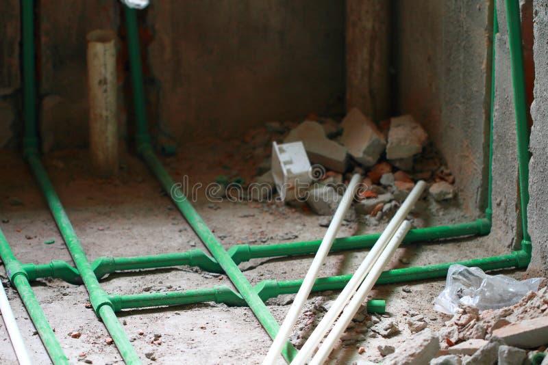 改造工程,在墙壁埋没pvc管子 免版税库存照片