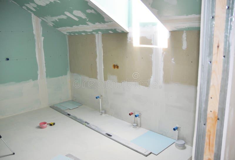 改造有干式墙修理的顶楼卫生间,涂灰泥绘画,粉刷 卫生间修理和整修 图库摄影