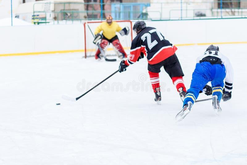 攻击的年轻溜冰者人 冰球比赛 库存照片