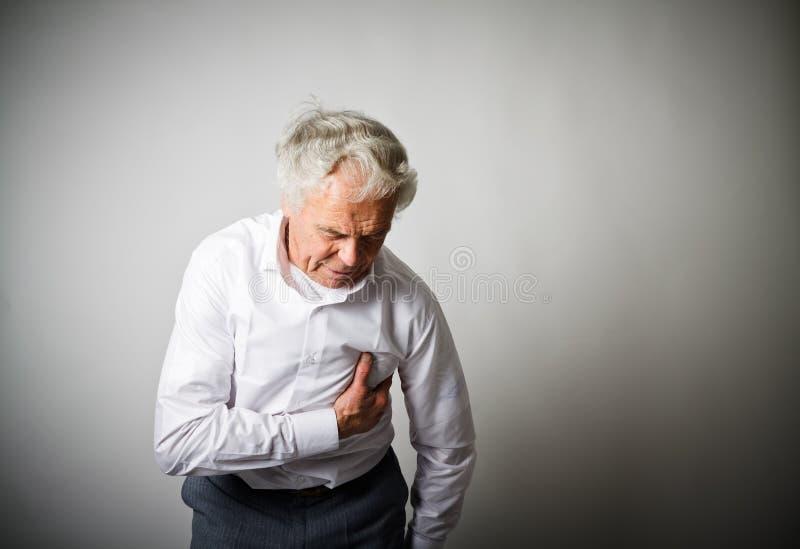 攻击重点保留人 充满胸口痛的老人 库存照片