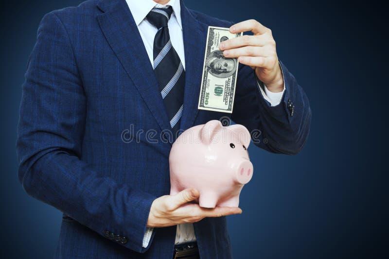 放一百美元的商人入存钱罐 在衣服的商人拿着存钱罐 财务储款概念 库存照片