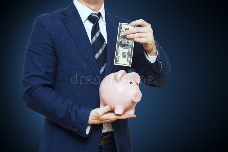 放一百美元的商人入存钱罐 在衣服的商人拿着存钱罐 财务储款概念 免版税库存照片