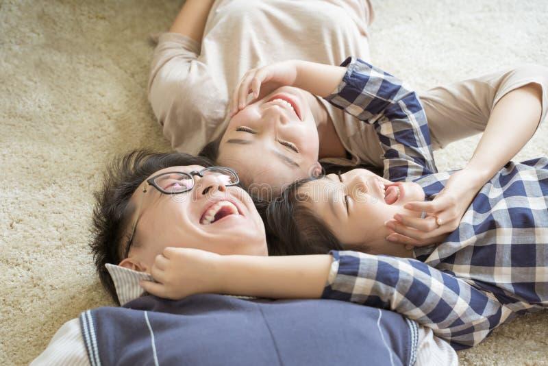 放下和使用在客厅的画象愉快的亚洲家庭 库存图片